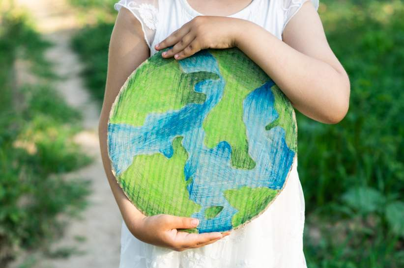 A child holding a cardboard cutout of the Earth